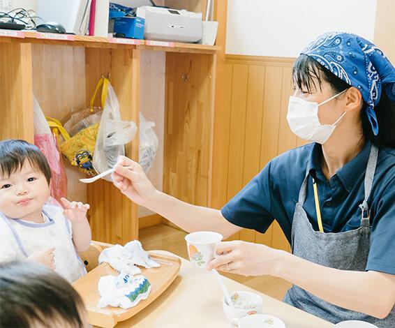 離乳食を食べるこどもと保育教諭